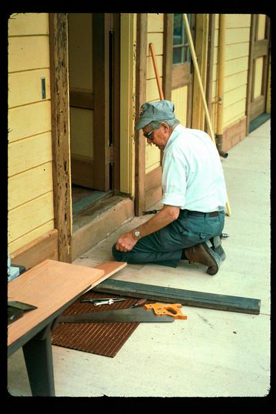 Gene Allen repairs Freight Office door threshold, 1992. acc2005.001.1608