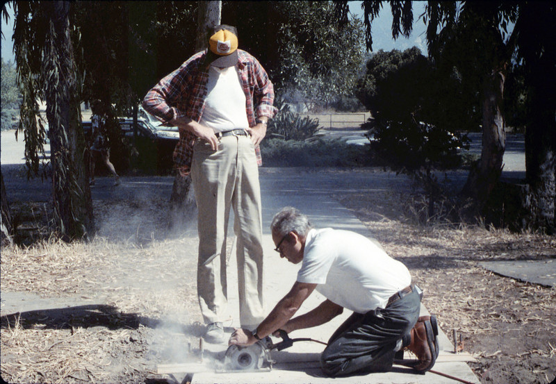 Ray Baird watches as Ralph Moore cuts the sidewalk for the miniature-railroad crossing, 6/1987. acc2005.001.0803