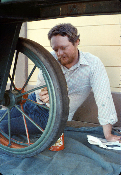 Doug Conrow paints baggage cart wheels, Work Day, 3/1988. acc2005.001.0908