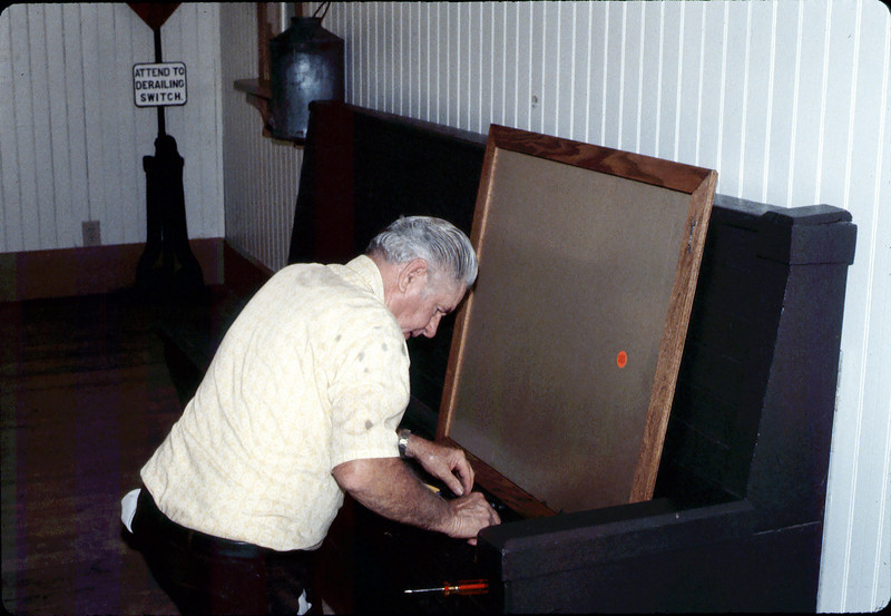 William Shrives installs the Depot Friends Plaque in Waiting Room. Bill built the frame, too., 1984 acc2005.001.0454