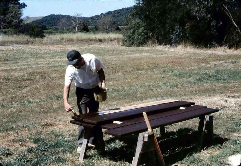 Ralph Moore paints a picnic table he built and donated to the museum, 1984. acc2005.001.0453A