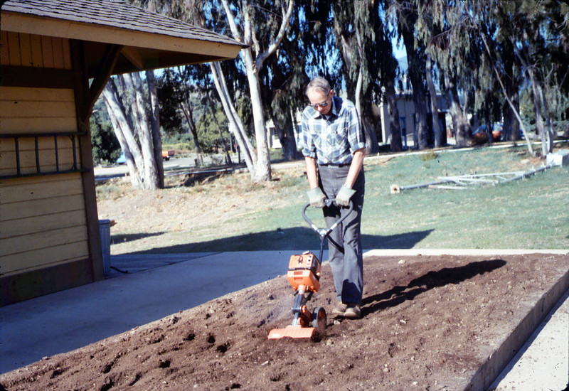 Gene Allen tills the soil in front of the Chamber of Commerce offices, 12/1986 acc2005.001.0661