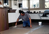 John Morelli applies new flooring in Freight Office, 9/1983. acc2005.001.0410