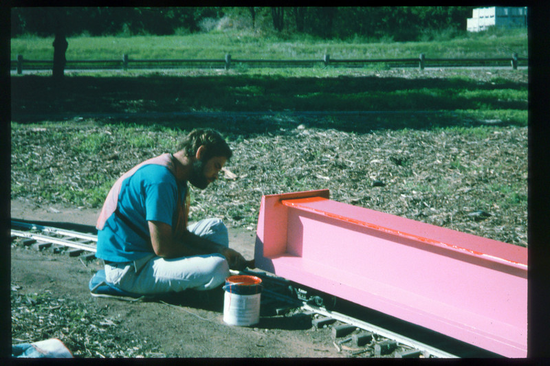 County SWAP worker applies red paint to passenger car in preparation for 1996 Candy Cane Train event. acc2005.001.2119