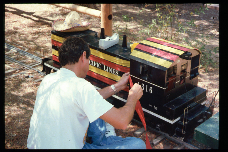 "John Locke helps decorate ""El Tren de la Fiesta,"" Aug. 6, 1994. acc2005.001.1990"