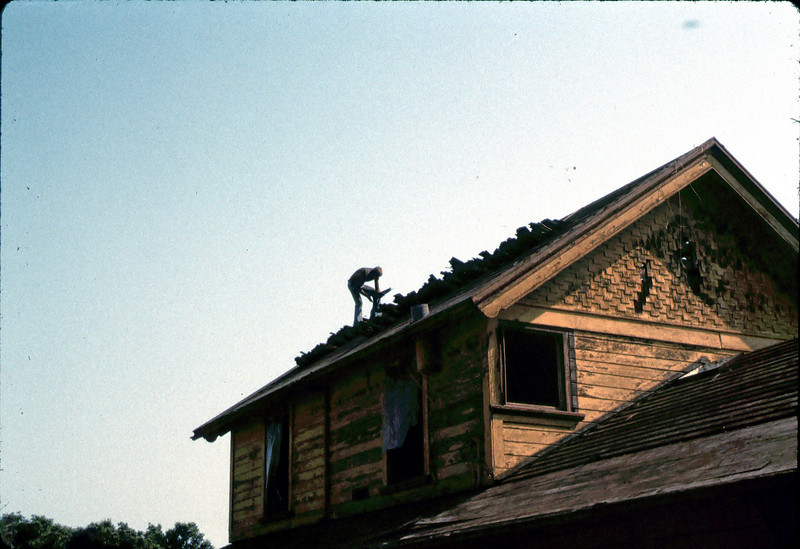Fireman assists in roof-removal effort, 6/1982. acc2005.001.0236