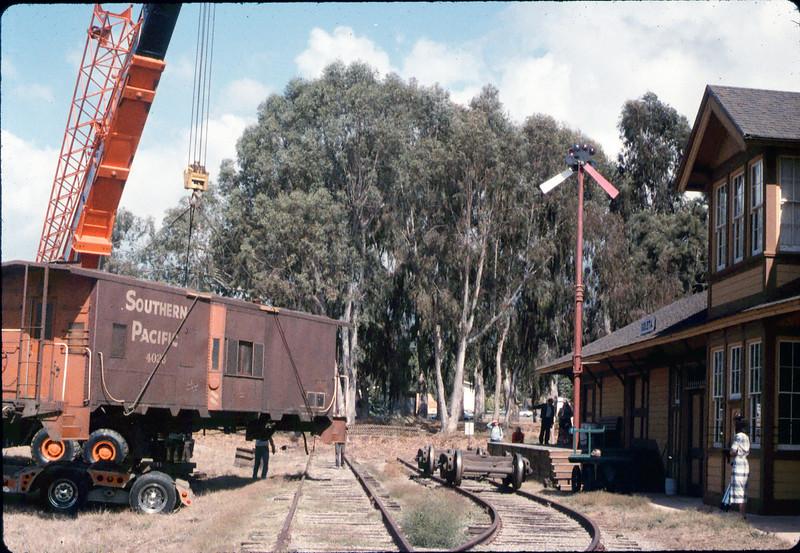 Crane raises caboose body while trucks wait on museum tracks, 9/25/1986 acc2005.001.0637