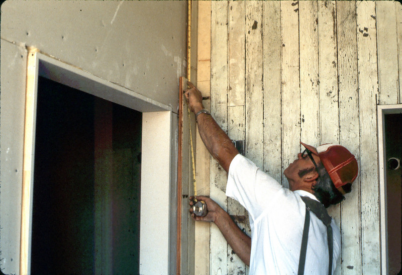 Carpenter Ralph Moore restores paneling in Waiting Room, 9/1982. acc2005.001.0327