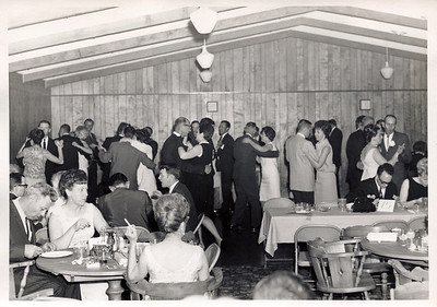 "The main banquet room.  Wood paneling and high ceiling.  Yes, those are the same round tables we had up until a couple years ago.  I guess we got our monies worth on those!  Lots of people in this photo that I can ""maybe"" identify, but none that I'm 100% sure of so I won't even try."