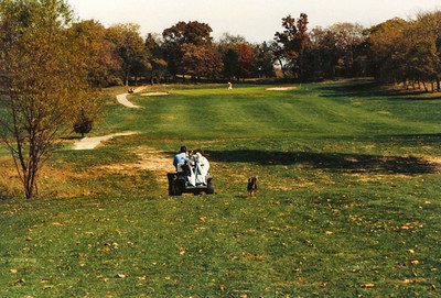 Maurice and Jane Niemann heading down the fairway with their faithful dog following along.  This is hole #1 and there's lot's of points of interest in the image.  Notice no top on the golf cart.  This was the norm for several years before we added tops to our fleet. There are only patches of cart path in critical locations, mostly around tees and greens.  It would be 1995 before we completed the continuous loop of path all the way around the course.  This is the old, original green that was basically a flat surface that sloped rather severely from back to front. The bunker on the left is the far left bunker today.  And, notice the grass is still cool season bluegrass/fescue.  This was prior to the introduction of bermuda.  Image taken about 1982/83.