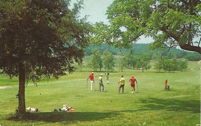 This postcard was found in an antique store in Wheatland, Mo in 1990.  It shows a group teeing off on the first tee. The golfers are thought to be (L-R):  Steve Fera, Mike Herbert, Alan Phillips (teeing off), golf professional Bob Bratzler, and Butch Amsberg.