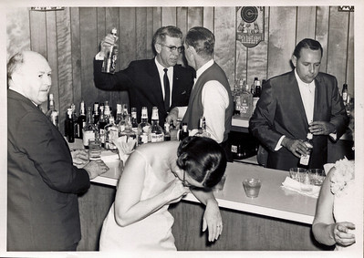 "The old members bar.  Buford Foster is the bartender in the dark suit holding up what appears to be a Seagrams bottle.  I can't identify any of the others.  An interesting note - see the numbers on some of the bottles?  At that time Camden County did not offer liquor by the drink.  You could buy beer or wine.  As a result, members brought their own bottles to the club and purchased ""set ups"", which was basically whatever you wanted to mix with your booze.  Bottles were identified by number."
