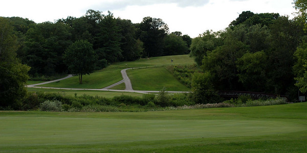 The view of the par 5 finishing  9th hole.  At the top of the cart paths is the landing area for first shot drives.  A creek protects the green making it difficult for roll-on approaches onto the green.