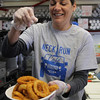 Marblehead, Ma. 4-14-17. Erica Petersiel salts some onion rings at the Neck Run Cafe on Ocean Street in Marblehead.