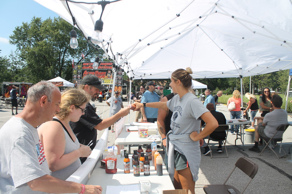 . Kristi Garabrandt - The News-Herald <br> Attendees at the Bob Golic Rib Burn Off in Willowick taste sauces from Golic\'s line of bar-b-que and wing sauces.