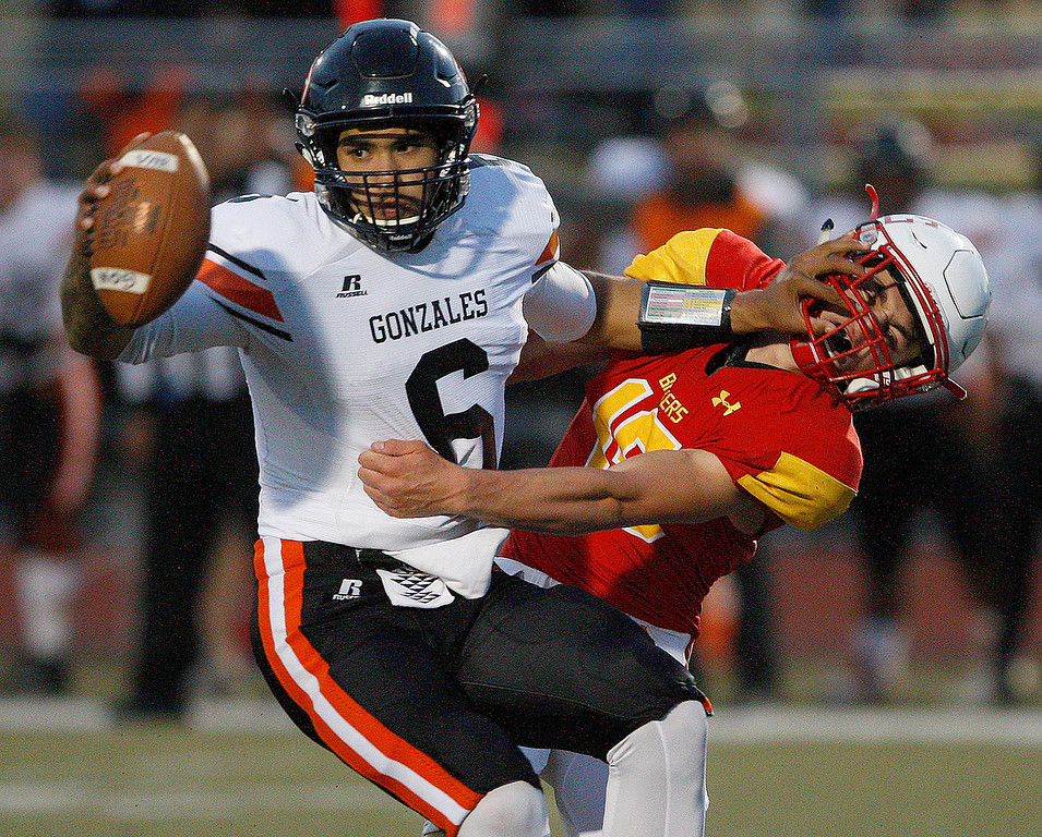 . Gonzales High School\'s Raul Morales (6) avoids the tackle by Pacific Grove High School\'s Ben Minik (15) during their game in Pacific Grove on Friday, August 31, 2018.  (Vern Fisher - Monterey Herald)