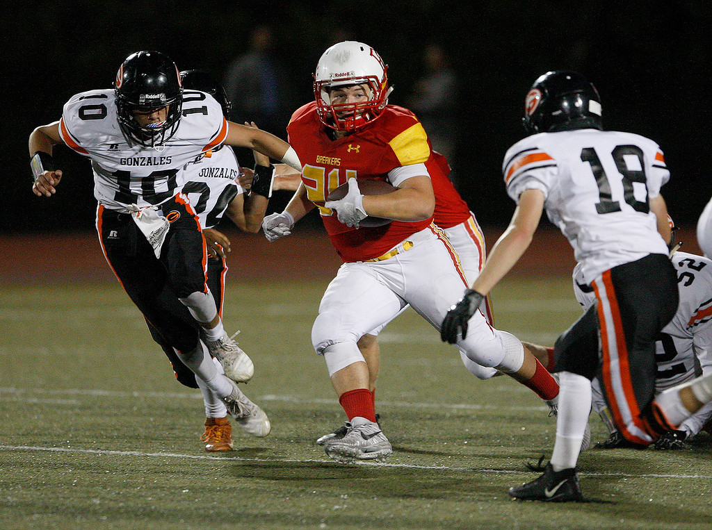 . Pacific Grove High School\'s Anthony DaSilva (24) avoids Gonzales High School defenders Jayson Flores (10) and Michael Duby (18) during their game in Pacific Grove on Friday, August 31, 2018.  (Vern Fisher - Monterey Herald)