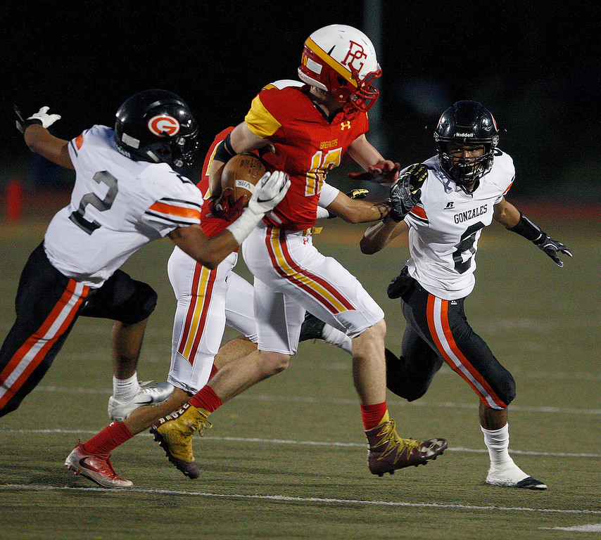 . Pacific Grove High School\'s Jake Haney (10) is brought down by Gonzales High School defenders Jose Lopez (2) and Franky Cisneros (8) during their game in Pacific Grove on Friday, August 31, 2018.  (Vern Fisher - Monterey Herald)
