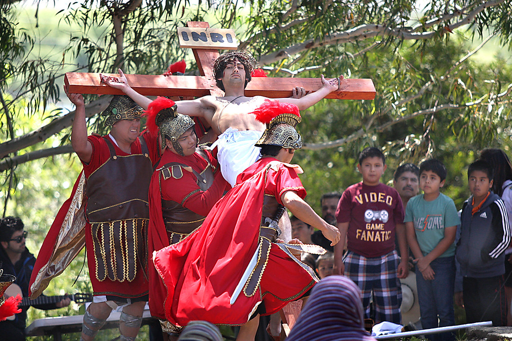 . Actors playing Roman soldiers raise a cross bearing another actor portraying Jesus Christ Friday, April 14, 2017, in Watsonville\'s Ramsay Park. Hundreds attended the annual Good Friday Passion Play staged by St. Patrick\'s Catholic Church commemorating the crucifixion of Christ.  (Dan Coyro -- Santa Cruz Sentinel)