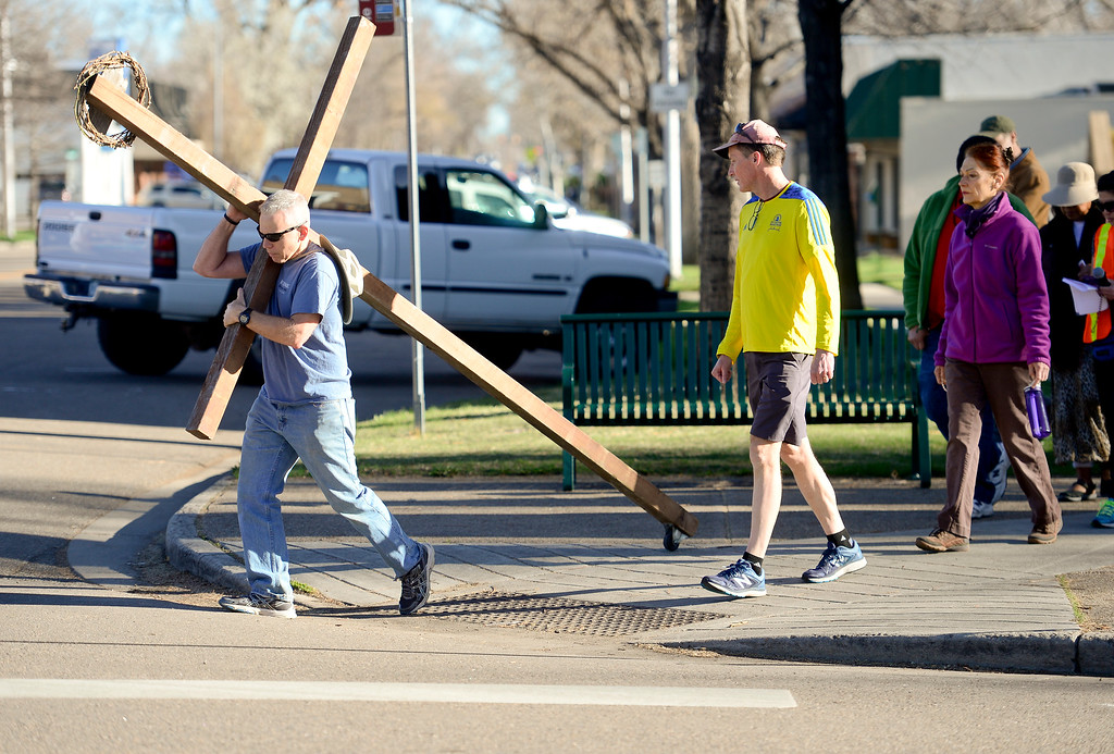 . LONGMONT, CO - APRIL 19:Tony Pardoe, of Longmont, carries the cross on 4th Avenue as he crosses Kimbark Street during the annual Good Friday Walk in Longmont on April 19, 2019. Pardoe built the cross that has been carried by members of the church for more than 10 years. (Photo by Matthew Jonas/Staff Photographer)
