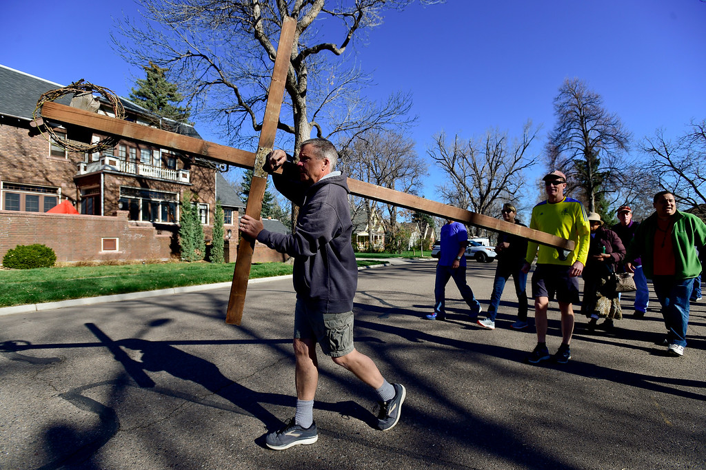 . LONGMONT, CO - APRIL 19:Tom Simmons, of Longmont, walks on Bowen Street while holding the cross during the annual Good Friday Walk in Longmont on April 19, 2019.  (Photo by Matthew Jonas/Staff Photographer)
