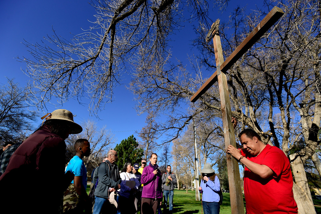 . LONGMONT, CO - APRIL 19:Pedro Solis, of Longmont, right, holds the cross and his rosary beads while at a stop at Thompson Park during the annual Good Friday Walk in Longmont on April 19, 2019. (Photo by Matthew Jonas/Staff Photographer)
