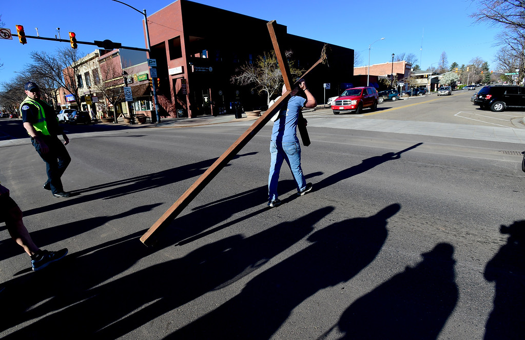 . LONGMONT, CO - APRIL 19:Tony Pardoe, of Longmont, carries the cross on 4th Avenue as he crosses Main Street during the annual Good Friday Walk in Longmont on April 19, 2019. Pardoe built the cross that has been carried by members of the church for more than 10 years. (Photo by Matthew Jonas/Staff Photographer)