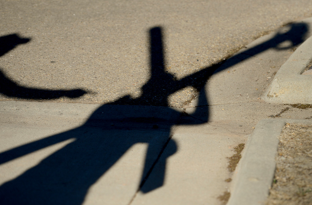 . LONGMONT, CO - APRIL 19:The shadow of Tony Pardoe, of Longmont, right, is seen on the pavement as he carries the cross during the annual Good Friday Walk in Longmont on April 19, 2019. Pardoe built the cross that has been carried by members of the church for more than 10 years. (Photo by Matthew Jonas/Staff Photographer)