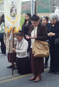 Woman pray during the Good Friday procession in Trenton . gregg slaboda photo