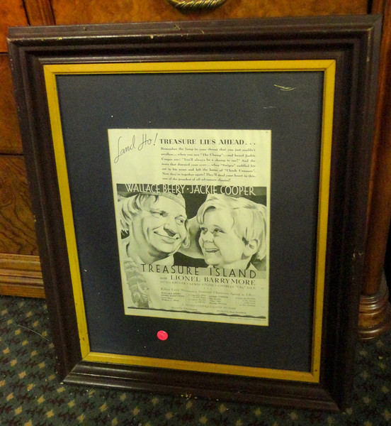 Treasure Island (1934) Framed Movie Poster.  For many people, this 1934 version is the definitive Treasure Island: the great chemistry between Wallace Beery and Jackie Cooper, the rousing pirate anthems, and the stubborn parrot on the shoulder. The pairing of the actors was a cinch, coming three years after their tremendously popular teaming in The Champ. Cooper plays Jim Hawkins, the English boy who discovers a treasure map amongst the possessions of one Billy Bones (Lionel Barrymore in a robust extended cameo), a pirate visitor to the Admiral Benbow Inn.  21 x 25.  <b>$40</b>