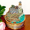 "Thomas Kinkade ""Sea Of Tranquility Lighted Music Box.  This is a Thomas Kinkade Second Issue in the Seaside Illuminations Music Box Collection. The Lighthouse and the House lights up.   It Plays the Tune "" From A Distance "" It also has the Bible verse Psalms 43:3 on the base.  This was put out by Thomas Kinkade Media Arts Group Morgan Hill Ca. Serial # A4299.  Very nice piece.  4 3/4 x 5.  <b>$30</b>"