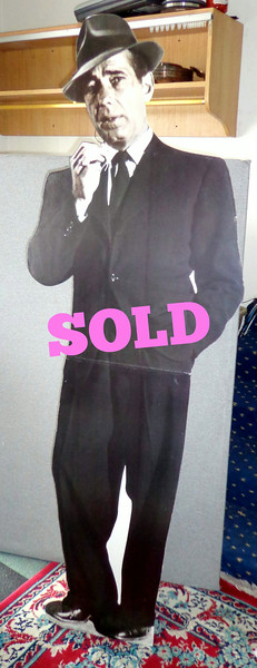 "Life-Size 6 Ft. Tall Humphrey Bogart Cardboard Cut-Out.  <i>""Here's looking a you, kid."" </i>   Humphrey Bogart... The man..  The legend..  Those were the days when an actor was something special. Of course, they didn't have the ruthless hordes of money grubbing paparazzi following them around every second like they do now,  As a result, the mystique still surrounds iconic figures like Bogart and further enhances his reputation even today.  On the other hand, if you own a retail business, this real-looking figure could serve as a 24hr. deterrent to crime.  You see, no one messes with ""Bogie.""  23 x 72.  <b>$35</b>"