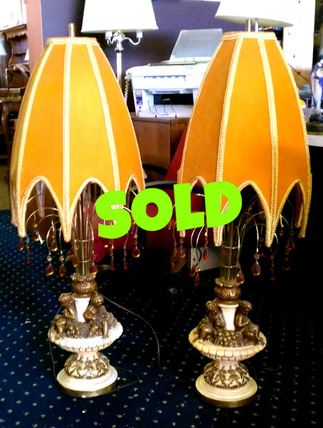 <b>Available at our Livernois Store Location - (313) 345-0884. </b>  Set of 2 Uniquely Styled French Provincial Table Lamps.  Make a dramatic statement of style and refinement when you add these 2 uniquely designed French Provincial table lamps.  These lamps feature brass cherubs and delicate adornments along with bold and compelling shades.  The set is in excellent condition and one of the finest sets we've had at our store in quite a while.   <b>$295 Purchased by Low Winter Sun.</b>