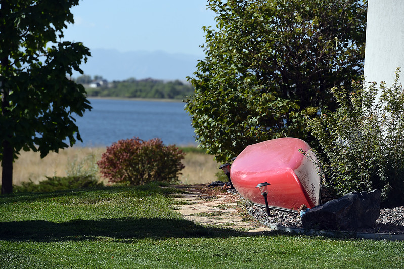 Jeromy Ginther's canoe rest in his yard with Lonetree Reservoir in the background Wednesday, Sept. 20, 2017, on Rabbit Run Lane southwest of Loveland. Ginther often sees people trying to access the reservoir with or without their own boats because Google Maps directs them to his street for access to the lake. The problem is that Google is wrong. It is not a public access to the lake, it's private property. (Photo by Jenny Sparks/Loveland Reporter-Herad)