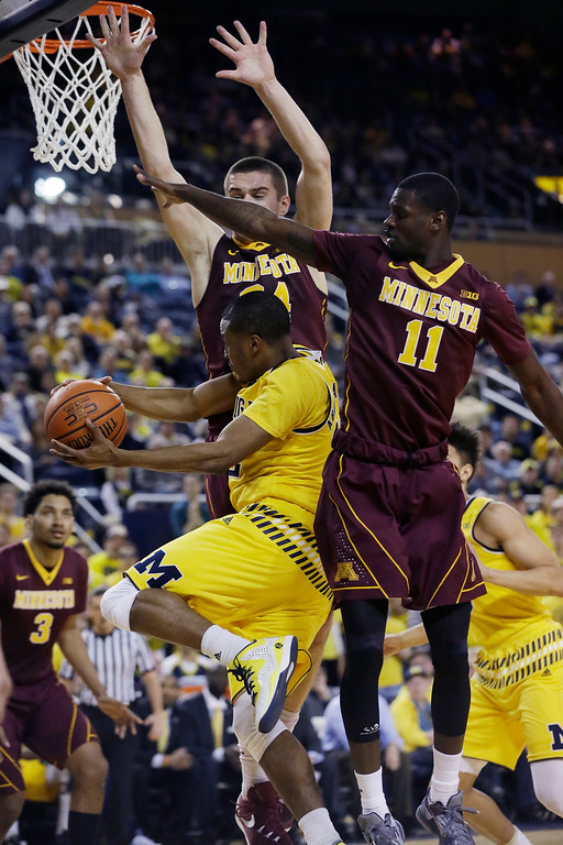 . Michigan guard Muhammad-Ali Abdur-Rahkman passes around the defense of Minnesota guard Carlos Morris (11) and forward Joey King during the second half of an NCAA college basketball game, Wednesday, Jan. 20, 2016 in Ann Arbor, Mich. Michigan defeated Minnesota 74-69. (AP Photo/Carlos Osorio)