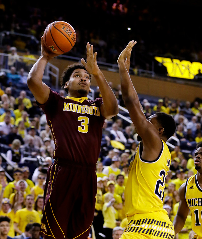 . Minnesota forward Jordan Murphy (3) shoots over the defense of Michigan guard Zak Irvin (21) during the first half of an NCAA college basketball game, Wednesday, Jan. 20, 2016 in Ann Arbor, Mich. (AP Photo/Carlos Osorio)