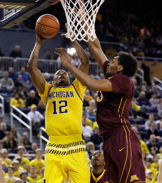 . Michigan guard Muhammad-Ali Abdur-Rahkman (12) shoots over the defense of Minnesota forward Jordan Murphy during the second half of an NCAA college basketball game, Wednesday, Jan. 20, 2016 in Ann Arbor, Mich. Michigan defeated Minnesota 74-69. (AP Photo/Carlos Osorio)