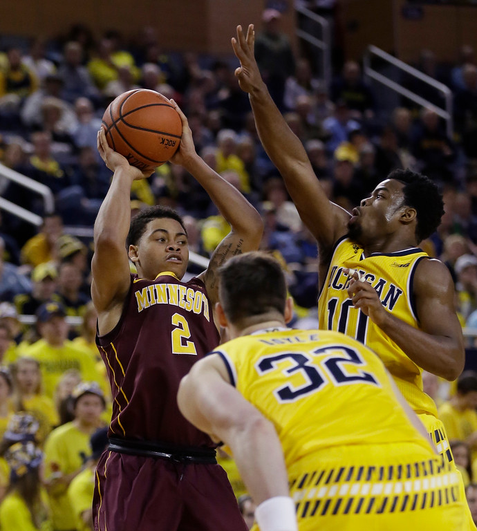 . Minnesota guard Nate Mason (2) looks to pass around Michigan guard Derrick Walton Jr. (10) during the first half of an NCAA college basketball game, Wednesday, Jan. 20, 2016 in Ann Arbor, Mich. Mason scored 25 points in the 74-69 loss to Michigan. (AP Photo/Carlos Osorio)