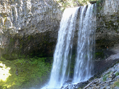 Tamanawas Falls  is another  favorite hiking place. It is an easy river side hike on about 30 minutes Notice the person hiking behind the water fall.To get there: Cross the Hood River bridge and go under the overpass and go right. Continue past Wind Dance and Tum-a-Lum. At the major intersection continue straight for about 30 minutes south on Hwy. 35  to Sherman Woods campground on hwy. 35. When you see Sherman Woods campground on the right make a U turn and drive 1/4 mile back to the first very long pull out. Park then hike to the right and cross a log bridge and keep to the right. Follow the signs. When you get to the falls look carefully and you will see a trail you can scramble up and go into a shallow cave behind the falls. Bring good shoes.
