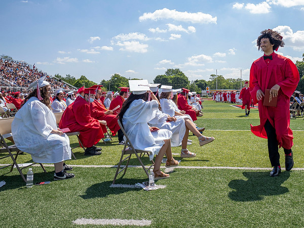 Goshen's London Hood, right, walks towards his seat after receiving his diploma during Sunday's Goshen High School Class of 2021 Commencement.