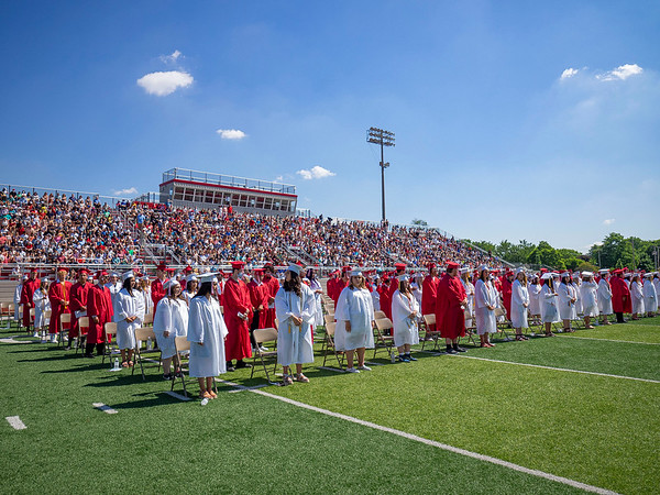 Goshen 2021 graduates stand in front of their seats during Sunday's Goshen High School Class of 2021 Commencement.