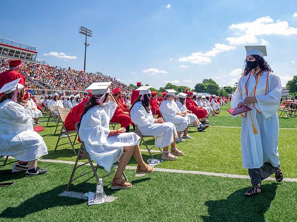 Goshen's Jasmine Frayre, right, walks back to her seat after recieving her diploma during Sunday's Goshen High School Class of 2021 Commencement.