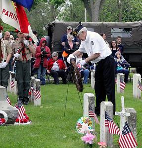 Roger Schneider | The Goshen News  Terry Morgan, Vietnam War veteran, places a wreath in the veterans section of Oakridge Cemetery Monday morning.