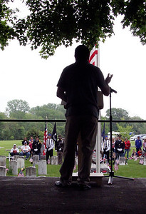 Roger Schneider | The Goshen News Featured speaker at Goshen's Memorial Day service at Oakridge Cemetery, Harold Eichhorn, is silhouetted on the lectern as attendees listen to his story of serving two tours overseas with the National Guard and his struggles with depression and PTSD since returning.