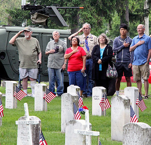 Roger Schneider | The Goshen News A group of onlookers salute and cover their hearts as the national anthem is played during Goshen's Memorial Day service at Oakridge Cemetery.