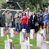 Roger Schneider | The Goshen News<br /> A group of onlookers salute and cover their hearts as the national anthem is played during Goshen's Memorial Day service at Oakridge Cemetery.