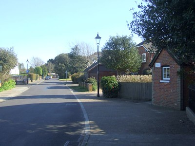 View southeast along Crescent Road. The cycleway (the southern extent of surviving trackbed) is on the left, level with the driveway on the right. The brick building on the extreme right is part of Admiralty Cottage, a private residence for c.100 years, but until the Stokes Bay line closed at the end of October 1915, this was the gatekeeper's residence. 22nd March 2015.