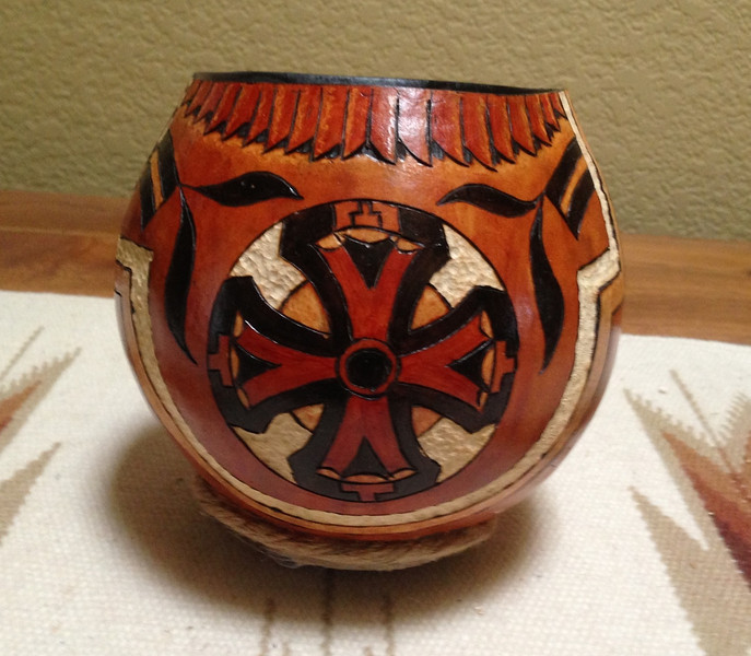 small gourd sports a hemp coil at the bottom, a burned and painted design with carving. The interior is black.