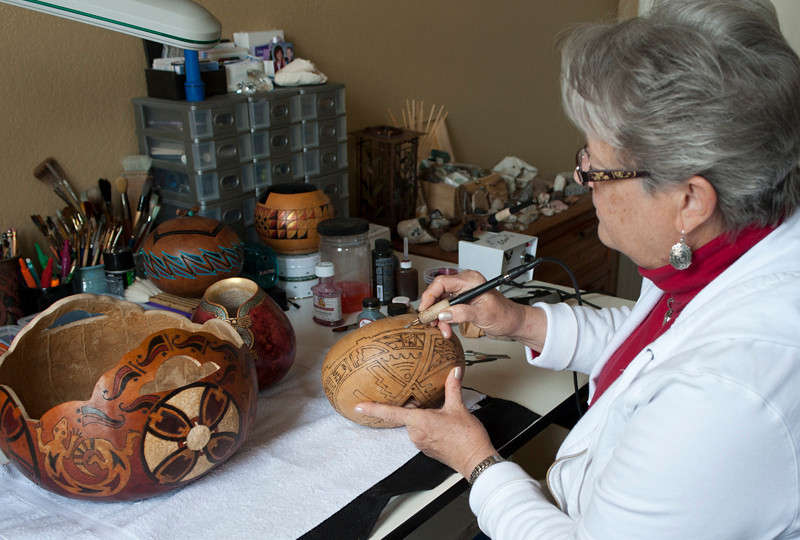 Using a wood burning tool to 'draw' the design onto the gourd.