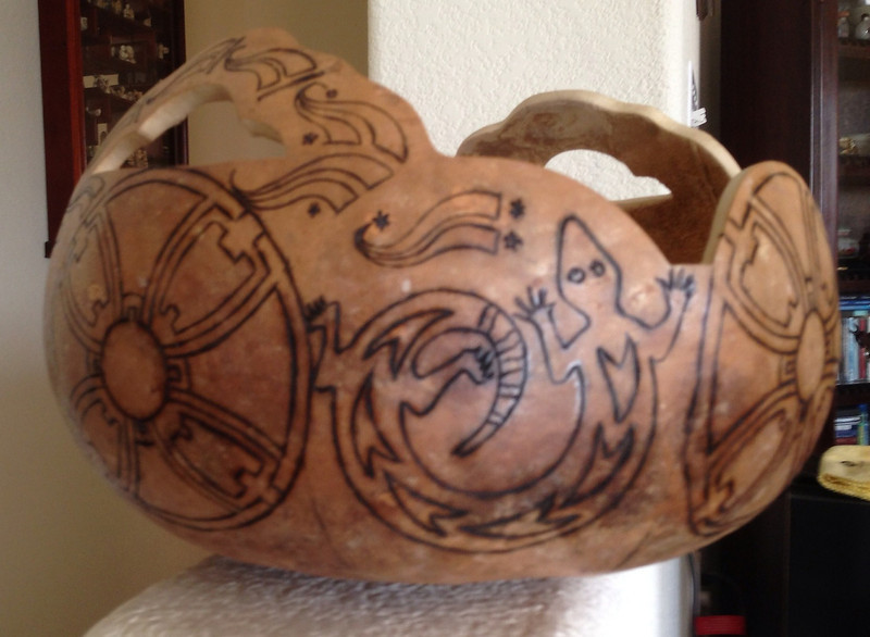This shot shows another gourd after cutting the shape and woodburning the design, ready for paint.